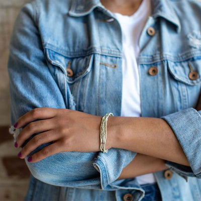 woman with pink nail polish wearing denim jacket and white tee shirt, with seed + barrel bracelet on left wrist