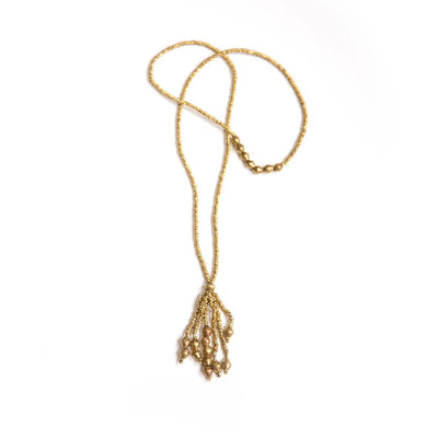 clasped golden tassel bead necklace on white backdrop