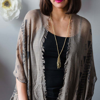 woman with pink lipstick, rustic cardigan and black tee shirt wearing tassel necklace, gold