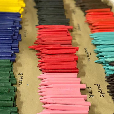 assorted eco friendly crayons. colors visable include green, blue, pink, purple, seafoam, orange, black, red