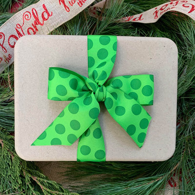 white compostable package wrapped in green polka dot ribbon and bow, with pine background