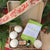 holiday themed background, includes 4 dryer balls, hand soap wrapped in twine, essential oil bottle, and green package of 32 dryer sheets