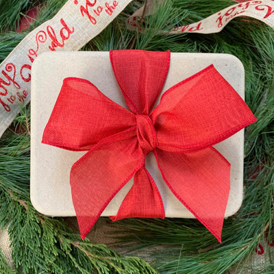 white compostable package wrapped in red ribbon and bow, with pine background