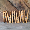 6 clothespins displayed vertically in front of rustic reclaimed wood