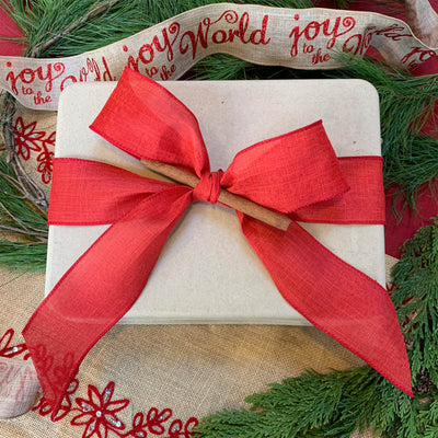 compostable package wrapped in red ribbon and bow