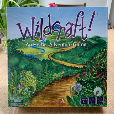 Wildcraft game. board game box. purple text with watercolor painting of vista