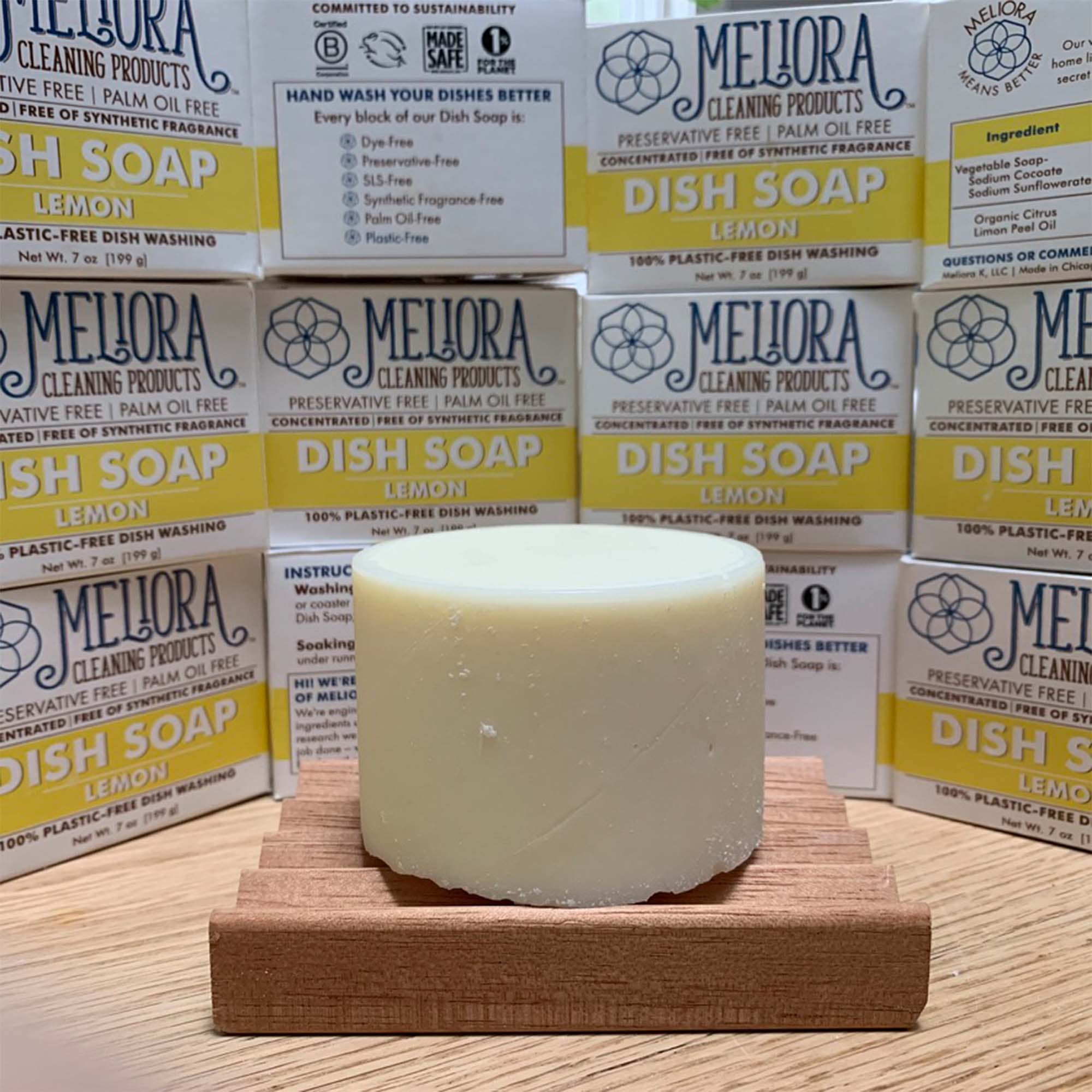 7 oz dish soap cylinder on wood table top, surrounded by meliora dish soap packages