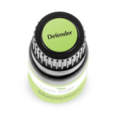 "birds eye view of black bottle with green label. reads ""defender"""