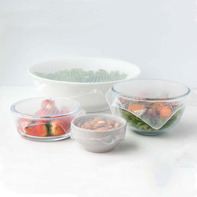 four bowls, 2 ceramic, 2 glass, varying sizes. filled with strawberry, almonds, salad, and greens. each bowl has a translucent silicone food cover