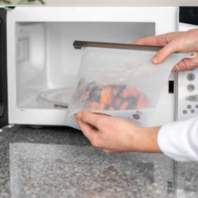 hand with white sleeves placing sealed food storage bag containing sweet potatoes in white microwave.