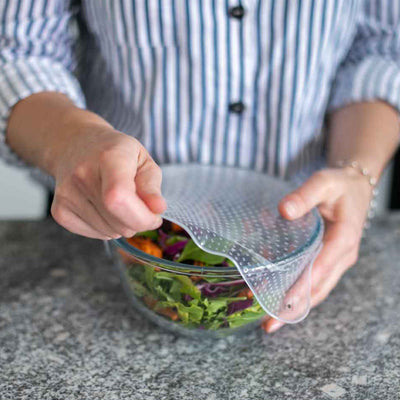 man wearing blue striped shirt and bracelet stretching silicon food cover over bowl containing salad