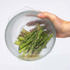 hand holding glass bowl with chopped asparagus. bowl has silicon food cover on top