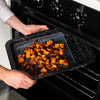 hands placing roasted sweet potato into oven with oven tray and silicon food cover underneath food.