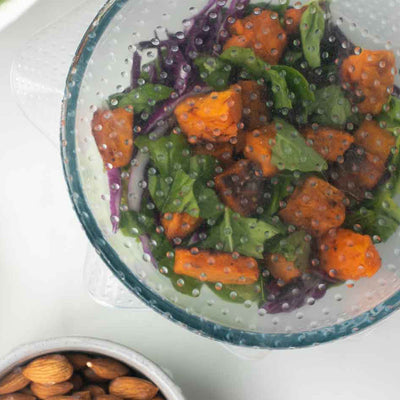 close up of glass bowl containing salad and almonds, with silicon food cover on top of bowl