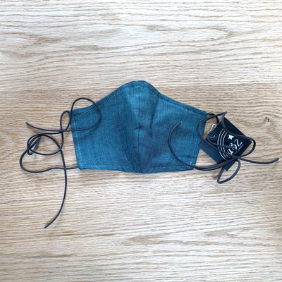 blue denim elastic free face mask on wood table top