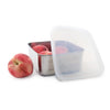 square stainless steel container with rounded corners and plastic lid ajar. container filled ripe peaches