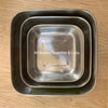 three square stainless steel containers with rounded corners all nested together on wooden table top