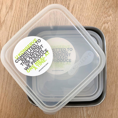 "square stainless steel container with rounded corners and plastic lid ajar. lid reads : ""u-knoserve committed to reducing the amount of trash we produce one meal at a time"""