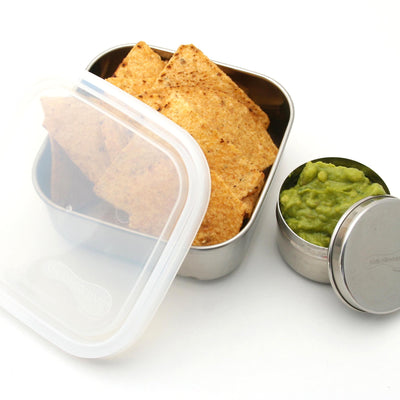 stainless steel container, lid ajar, container filled with guacamole, tortilla chips in 2nd rectangular stainless steel container.