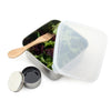 square stainless steel container with rounded corners and plastic lid ajar. container filled spring mix salad and wooden fork. small round stainless steel container filled with balsamic dressing, lid ajar