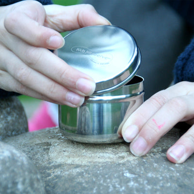 1 hand holding small round stainless steel container, other hand lifting lid. outdoors, placed on rock
