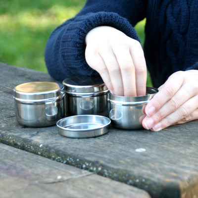 3 stainless steel containers, two hands in blue knit sweater pulling item out of one container with lid resting next to containers. outdoors on picinic table