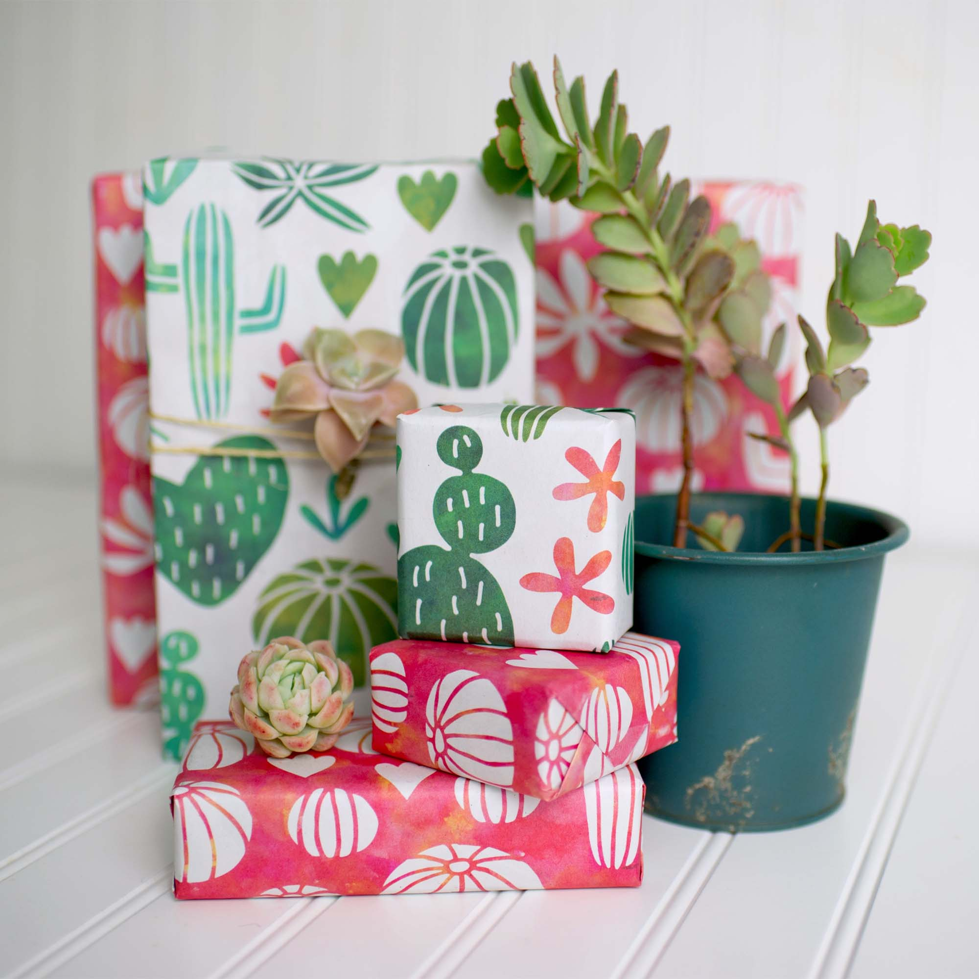 various sized gifts wrapped with wrappily paper. green and red succulent designs. reversible.