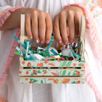 childs hands with pink nail polish holding miniature egg basket with eco-shred basket filler, blue green and white