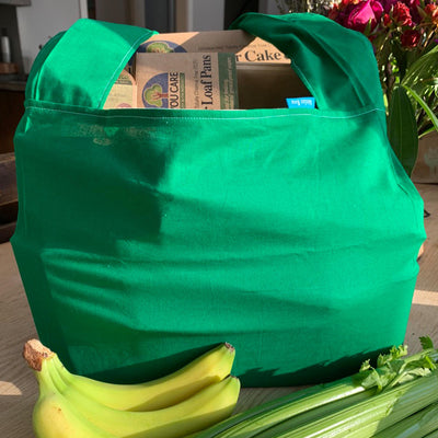 "shopping bag filled with cardboard ""if you care"" products. green color, surrounded by banana and celery"