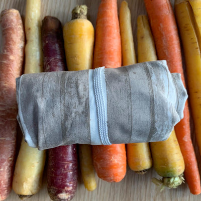 rolled up barn wood design plastic free shopping bag with white elastic, displayed over multicolored carrots