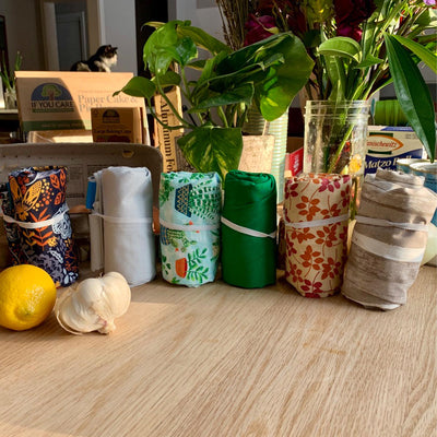 6 plastic free shopping bags, rolled with with white elsactic, on wood table surrounded by plants and groceries