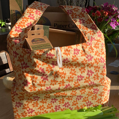 "shopping bag filled with cardboard ""if you care"" products. pink orange flower design"