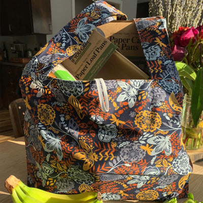 "orange, white and yellow floral design shopping bag filled with cardboard ""if you care"" products."