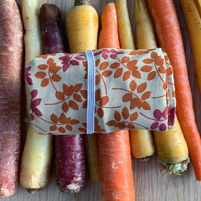 rolled up pink and orange flower design plastic free shopping bag with white elastic, displayed over multicolored carrots