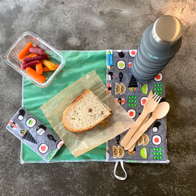 sushi design place mat on concrete, with que collapsable water bottle, wooden cutlery set, glass container with carrots, and sandwich on wax paper