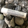4.25g lib balm tube displayed over assorted rocks. list of ingredients and recommended uses visible