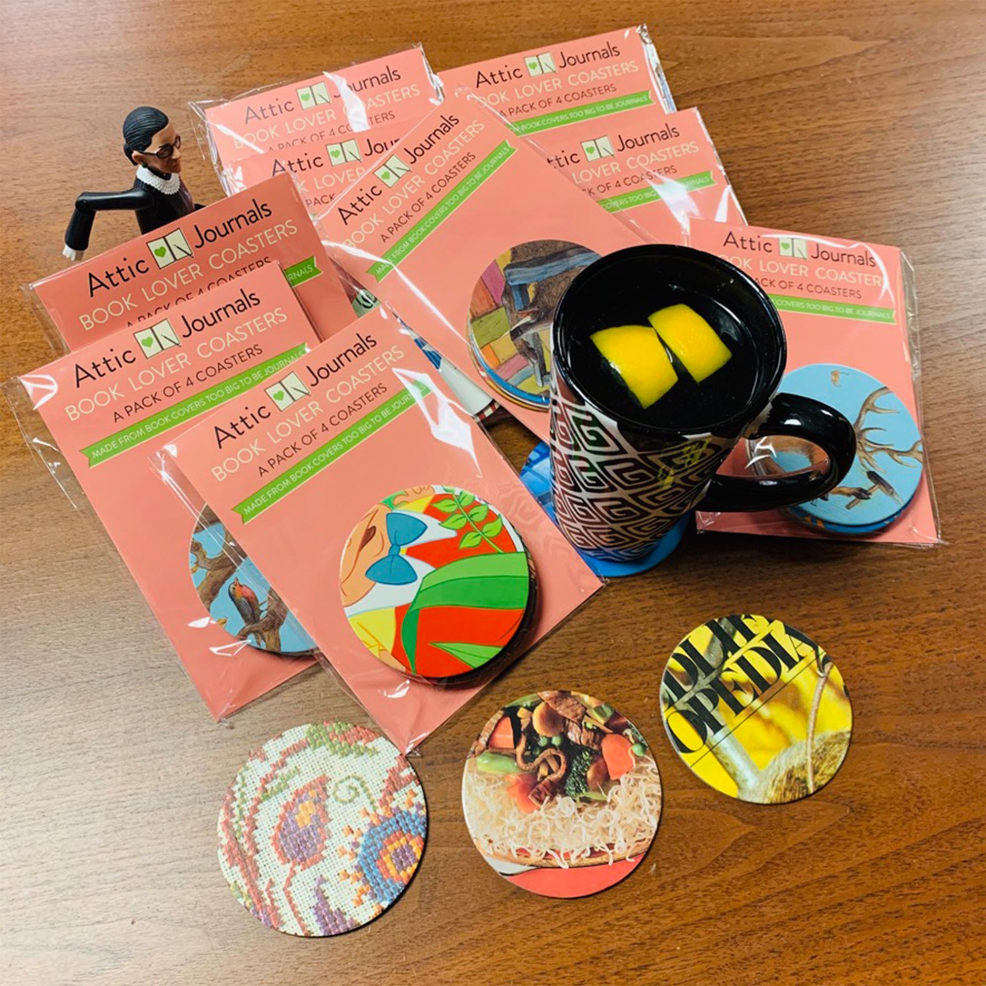Packages of drink coasters made from recycled board books. Variety of colors and patters.  A mug with water and lemon is sitting on one coaster, and a figure of Ruth Bader Ginsburg is placed  between the packages