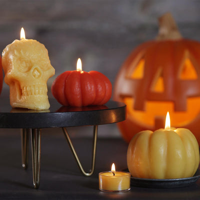 Yellow beeswax skull candle with lit flame, 2 small beeswax pumpkin candles with lit flame, small votive with lit flam and carved jack o lantern