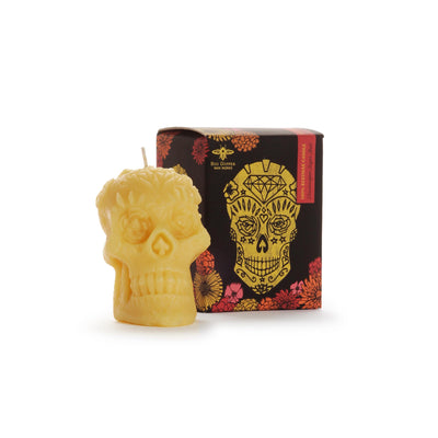 Yellow beeswax skull candle next to product box