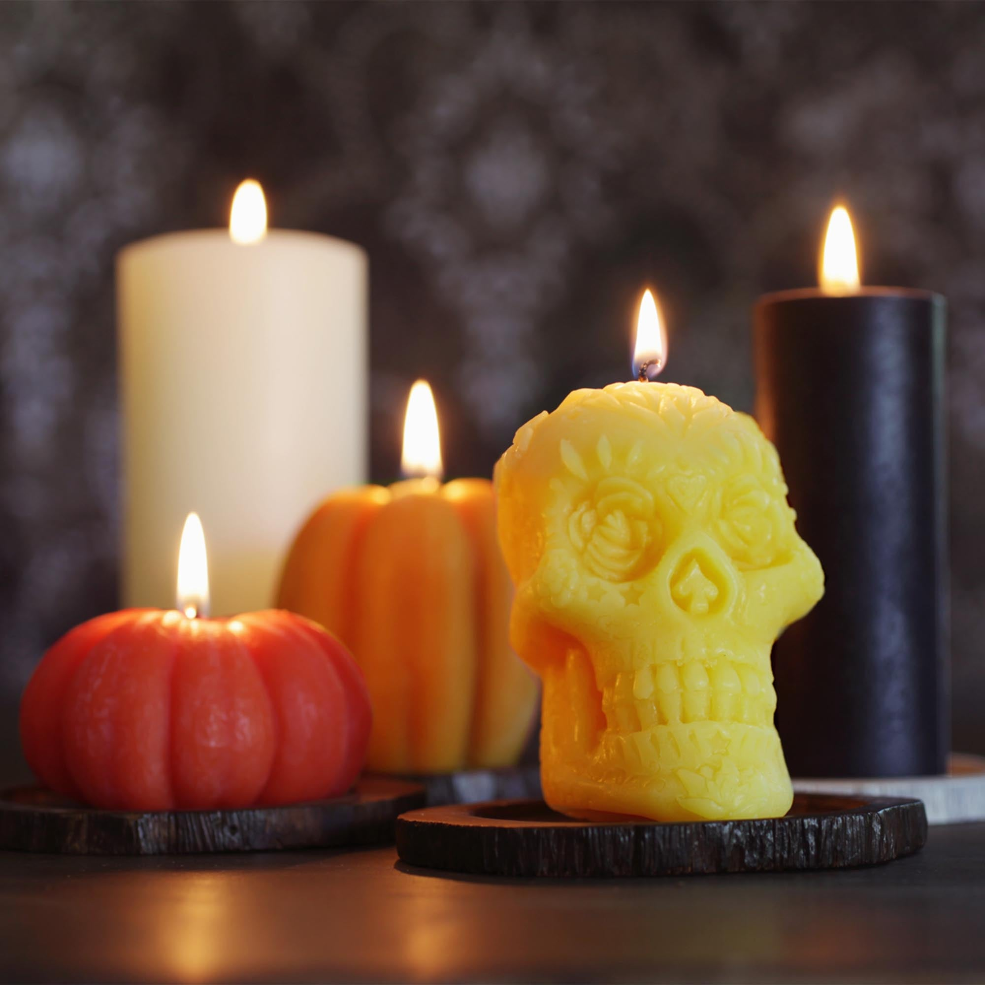 Yellow beeswax skull candle with lit flame, 2 small beeswax pumpkin candles with lit flame, black pillar candle with lit flame, white pillar candle with lit flame