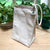 Light beige cotton lunch bag with rope handle, on a table with plants in the background