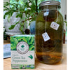 Organic Green Tea Peppermint by Traditional Medicinals®, net wt .85 oz, 16 wrapped tea bags, on wood table next to large mason jar filled with tea bags and iced tea