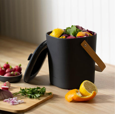 orange and lemon peels, baby radishes and a cutting board with cilantro and diced onion surrounding a black compost bin with a wooden handle. the bin is filled to the brim with fresh fruit and vegetable left overs, ready to be transported to compost pile