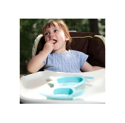 Child girl  with blue shirt sitting in highchair outdoors. her hand is in her mouth, enjoying food from teal dog shaped plate
