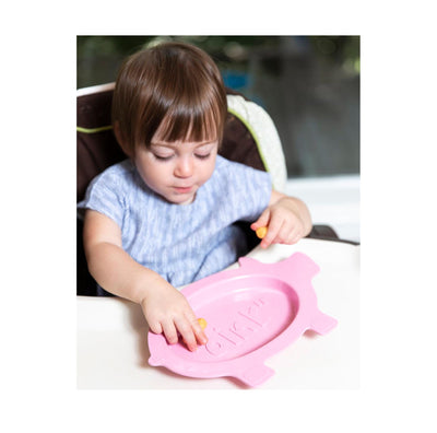 Child girl  with blue shirt sitting in highchair outdoors. orange food in each hand, enjoying food from pink pig shaped plate