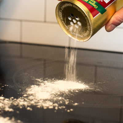 hand pouring bon ami from canister onto black stove top with white tile background