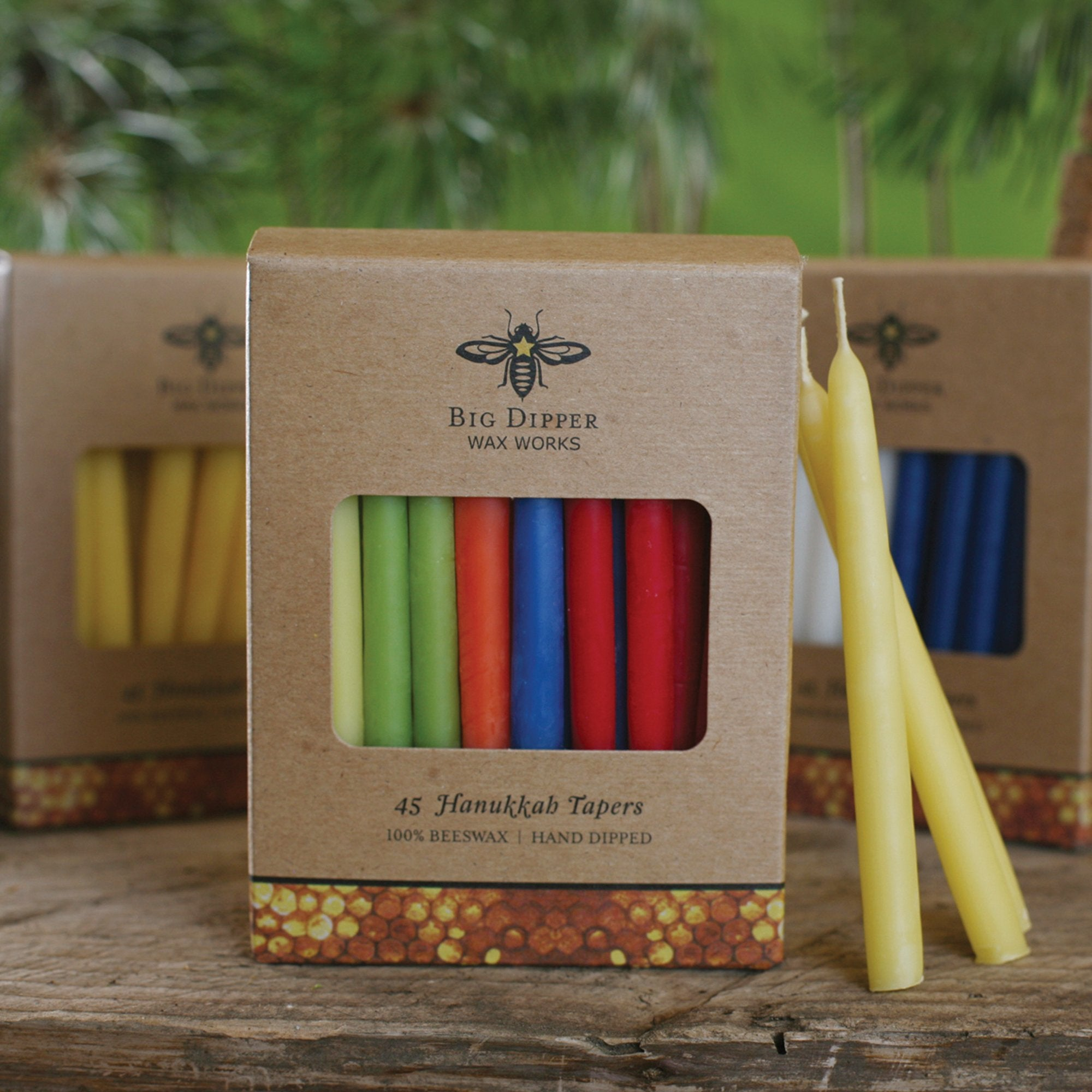 cardboard pack of 45 multicolored hanukkah tapered beeswax candles, dispalyed in front of two other packages on a wooden tabletop with a green forest backdrop