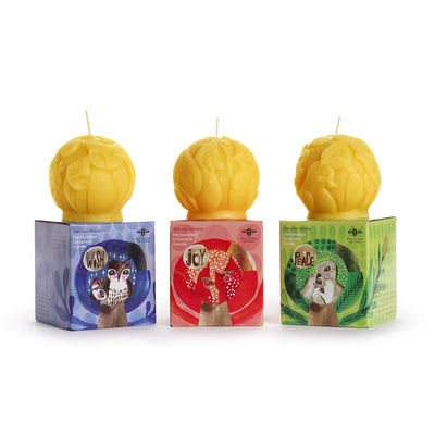 three sculpted naturally colored beeswax candles atop three packages. designs include doves, owls, cardinals.