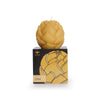 sculpted Lotus sphere candle, natural colored, sitting on top of black cardboard packaging, with golden lotus design on front