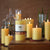 eight golden honey 100% Pure Beeswax Candles of different heights and widths, lit atop on ebony table top including succulents